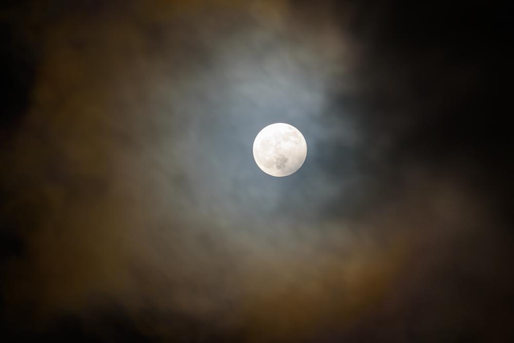 volle maan met kleureffect in de wolken