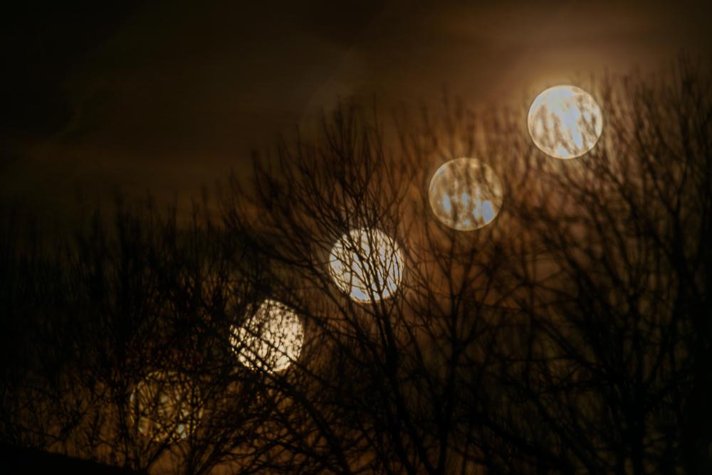 rijzende volle maan in bewolking
