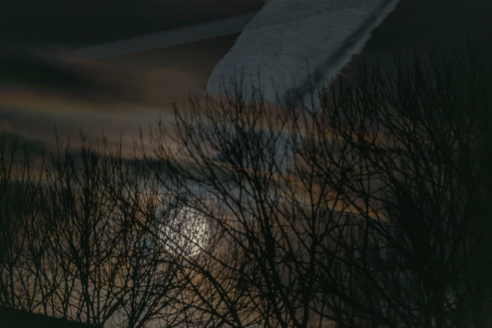 volle maan met vliegtuigstrepen in de lucht