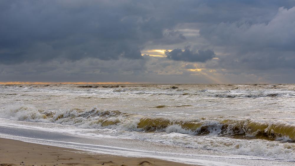 zon door de wolken op strand de koog texel