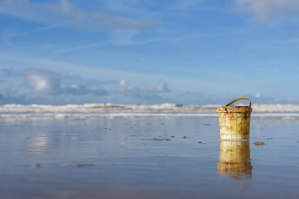 stilleven op strand met emmer.