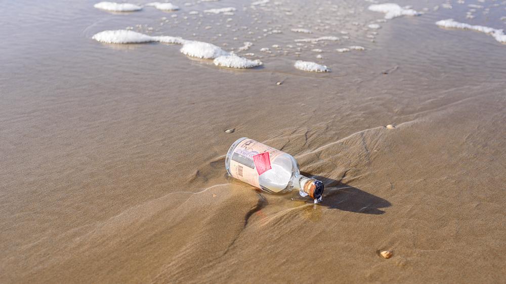 lege drankfles op het strand.
