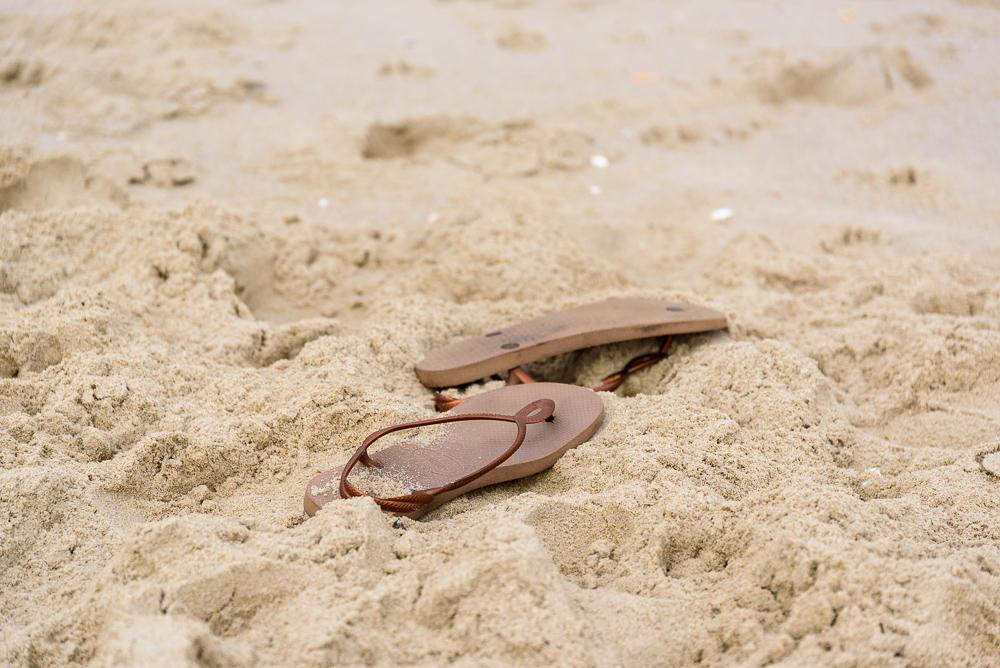 Slippers op het strand bij het palendorp.